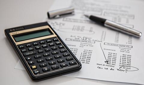 Calculator, pen on top of financial spreadsheet