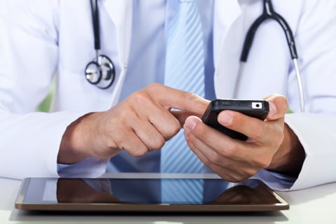 Doctor with table and smartphone