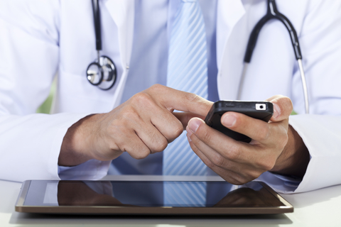 Doctor using cellphone and tablet