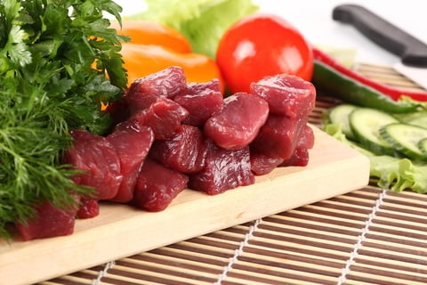 Raw meat and vegetables on a plate