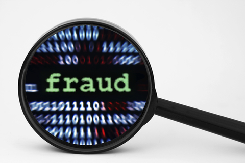 Magnifying glass highlighting the word fraud