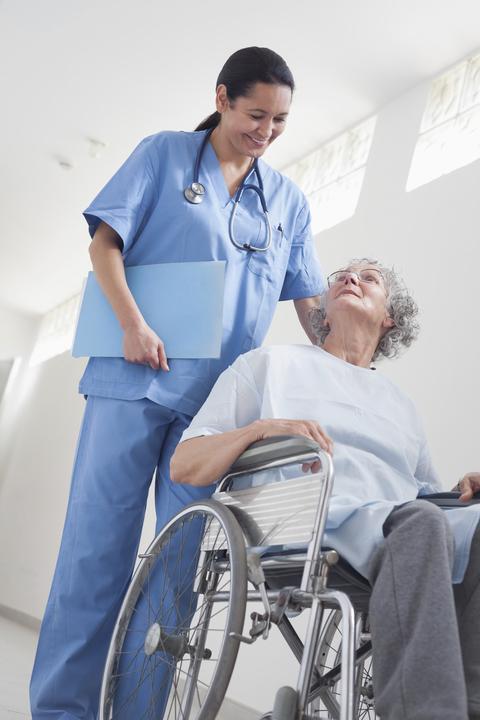 Nurse wheeling elderly patient down hall in wheelchair