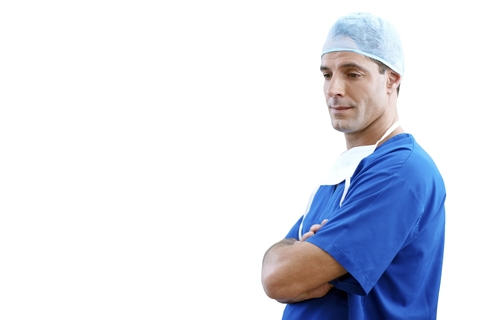 Doctor in surgical scrubs standing with his arms crossed
