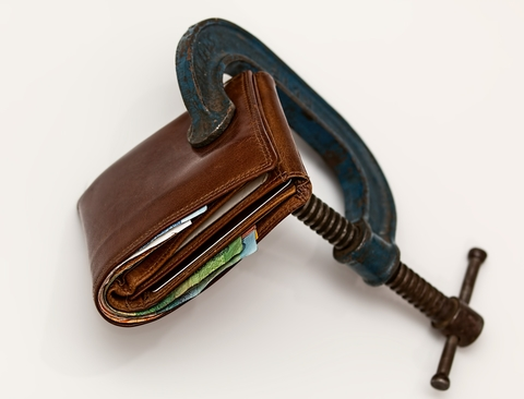Wallet being squeeze by a vice