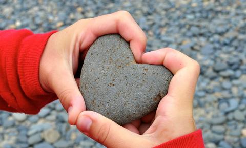 Hands holding a small rock shaped like a heart