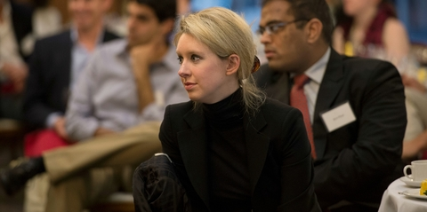 Elizabeth Holmes sitting at a table