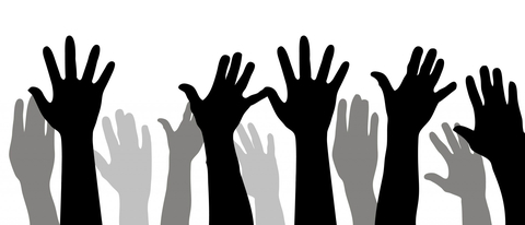 Shadows of multiple hands being raised in the air