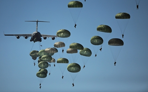 Many people jumping out of a plane with green parachutes