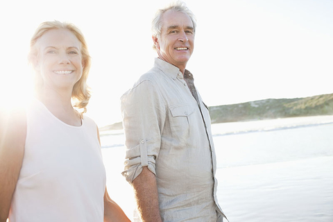 Older couple walking on a beach
