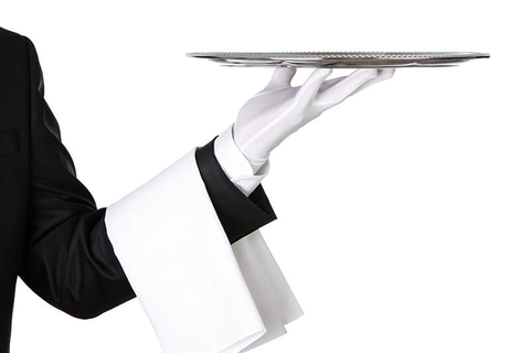Waiter holding silver platter - Nastco/iStock/Getty Images Plus/Getty Images