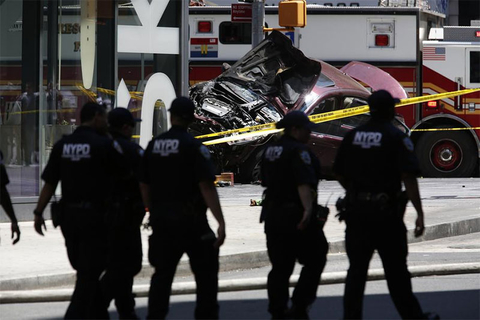 A smashed car sits on the corner of Broadway and 45th Street in New York's Times Square after ploughing through a crowd of pedestrians at lunchtime.