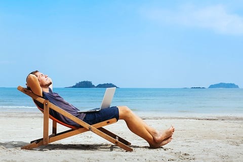 Businessman With A Laptop Relaxing On Beach