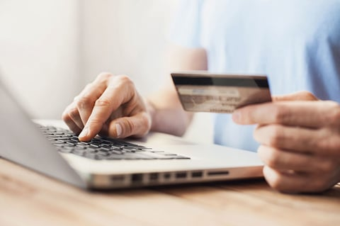 Young man shopping with credit card and laptop computer