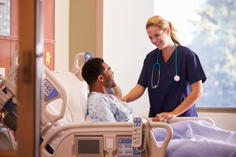 Female doctor talking to male patient in hospital bed