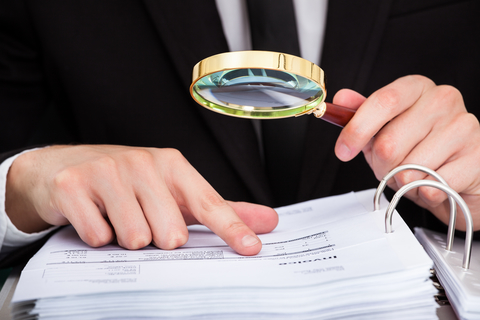 Man looking at documents with magnifying glass
