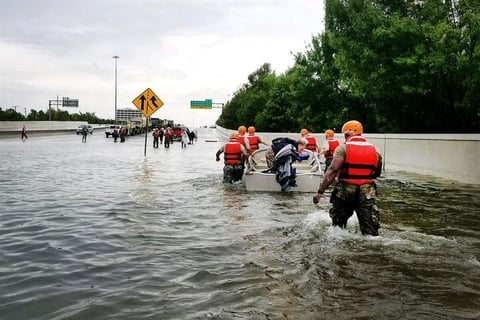 Rescue workers traverse floodwaters