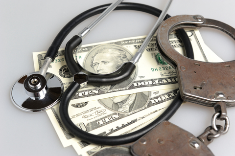 Money, handcuffs and a stethoscope