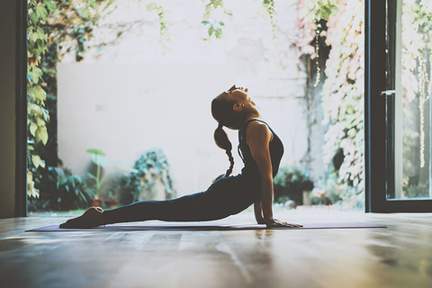 yoga instructor stretching in front of a garden