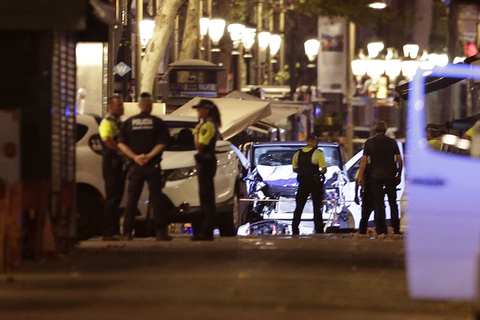 Police officers stand next to the van involved on an attack in Las Ramblas in Barcelona, Spain