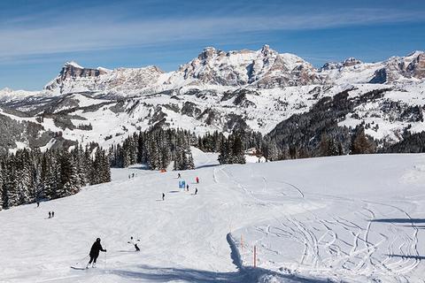 Skiers going down a mountain in Alta Badia Dolomites Italy