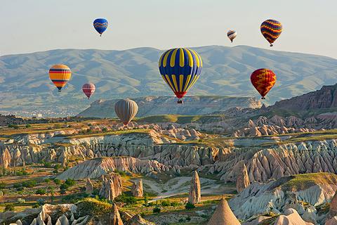 Colorful hot air balloons flying over the valley at Cappadocia, Anatolia, Turkey.