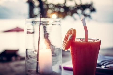 Close up of a cocktail and a candle in a mason jar at a Caribbean beach bar