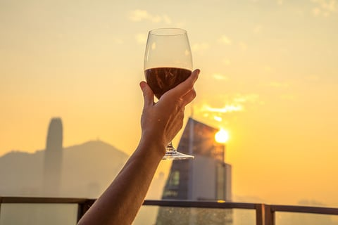 Close up of glass of red wine raised with the background the spectacular Hong Kong skyline at sunset.