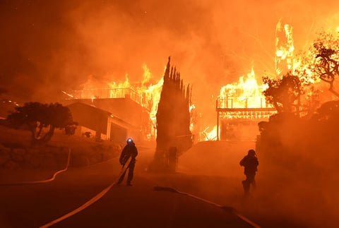 Firefighters work to put out a blaze burning homes in Ventura, California.