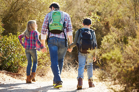 dad and children holding hands and hiking in the woods