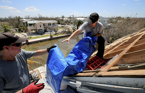 Bob Fiorile, 72, and Todd Brown, 42, right, pull a tarp onto the exposed roof of Fiorile's home in Big Pine Key.