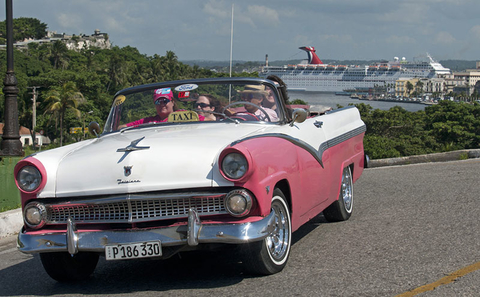 A classic car drives in Havana Cuba with Carnival Paradise in the background