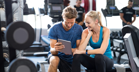 Couple in Gym Looking at a Tablet