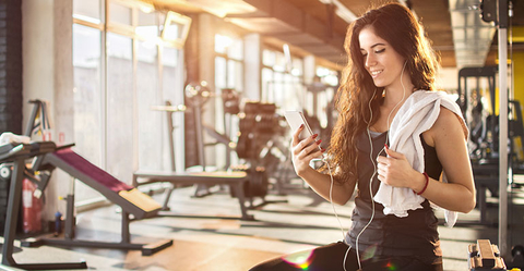 Woman on Mobile Phone in Gym