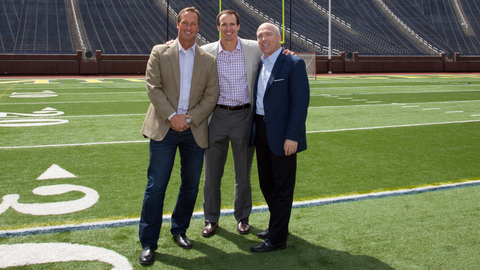 Title Boxing Club CEO John Rotche left New Orleans Saints quarterback Drew Brees center and PTMD Restaurants chairman David Barr right pose for a photo at Michigan Stadium in Ann Arbor Brees and Barr were added to the Title Boxing Club ownership group in May Photo courtesy Title Boxing Club International