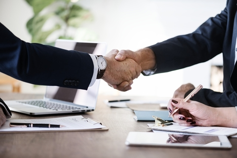 handshake over a desk with computers and someone taking notes