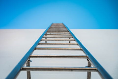 A ladder going up a side of a wall to the sky