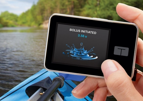 person in kayak holding Tandem insulin pump in one hand, screen says bolus initiated