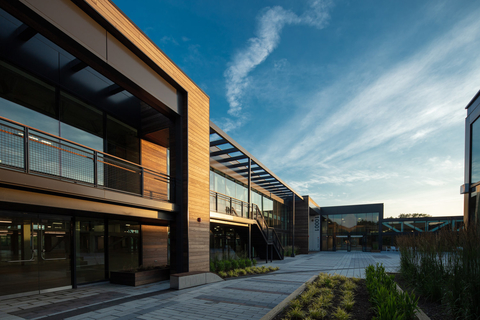 Exterior ElevateBio BaseCamp site in Waltham, MA: A modern building of glass, wood and metal with a courtyard and blue sky in the background