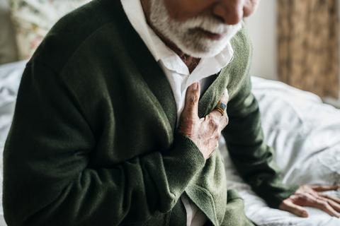 photo of elderly man having heart problems holding his chest
