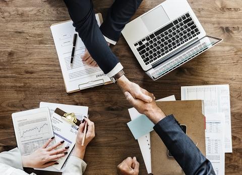 人们在桌子上握手,上面有电脑和纸张