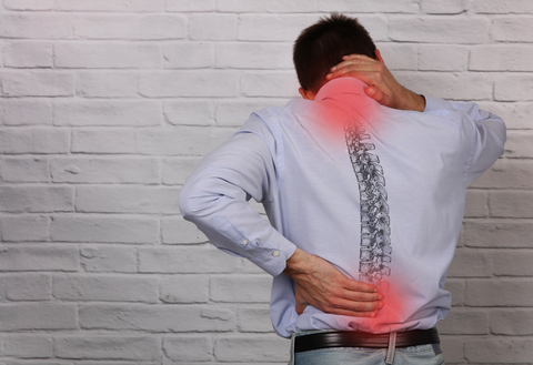 Back of man in long-sleeved shirt holding his neck and lower back. The places he's holding have red circles on them to indicate pain. An image of the spine is overlaid on his back.