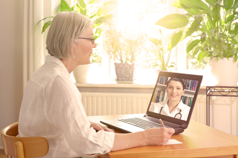 senior woman in front of laptop during virtual visit with doctor