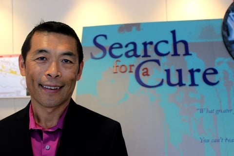 "Zhi Hong next to a banner that says ""Search for a cure"""