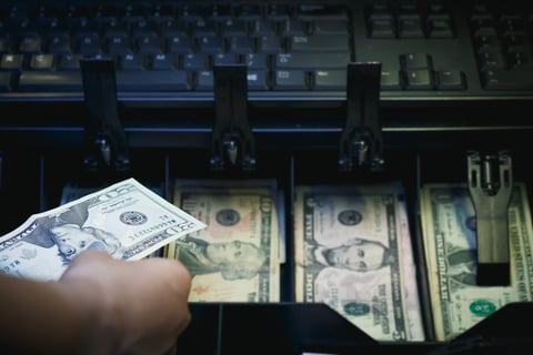 Hand reaching into or pulling out of cash register