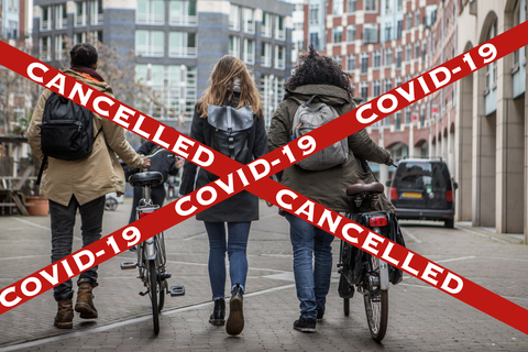 COVID-19 cancelled sign with young people walking