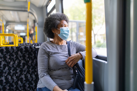 A woman rides a bus while wearing a face mask
