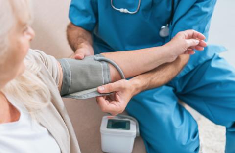 Doctor taking blood pressure of an older patient