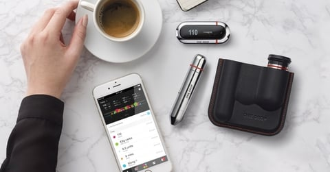Bird's eye view of One Drop app, lancet, blood sugar meter with a cup of coffee