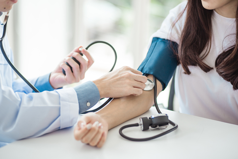 A doctor checking a patient's blood pressure