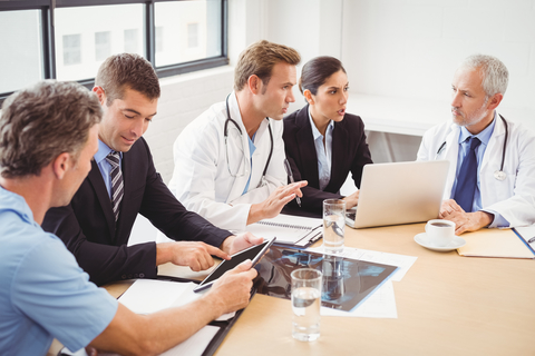 Doctors and businesspeople discussing in groups with computers